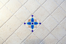 Beautiful Beige Tiles With Uneven Edges Are Laid Out Diagonally. Background. In The Center Is A Tile With A Blue Floral Pattern