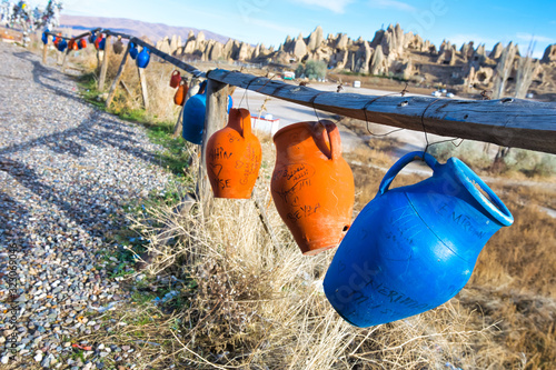 traditional hand made blue and brown pots with writings are hanging on the wires in a countryside of Cappadocia Wallpaper Mural