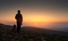 A Hiker And Their Dog Watching The Bright Orange Sunrise Over Bampton Common From The Summit Of Rampsgill Head In The Lake Distict UK.