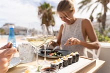 Girl Smiling Out Of Focus While Eating Pieces Of Shushi With Soy Sauce In A Terrance
