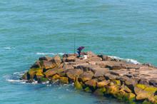 Fisherman On A Stone Wave Brea...