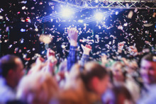 Colourful Confetti Explosion Fired On Dance Floor Air During A Concert Festival, Crowded Concert Hall With Scene Stage Lights, Rock Show Performance, With People Silhouette
