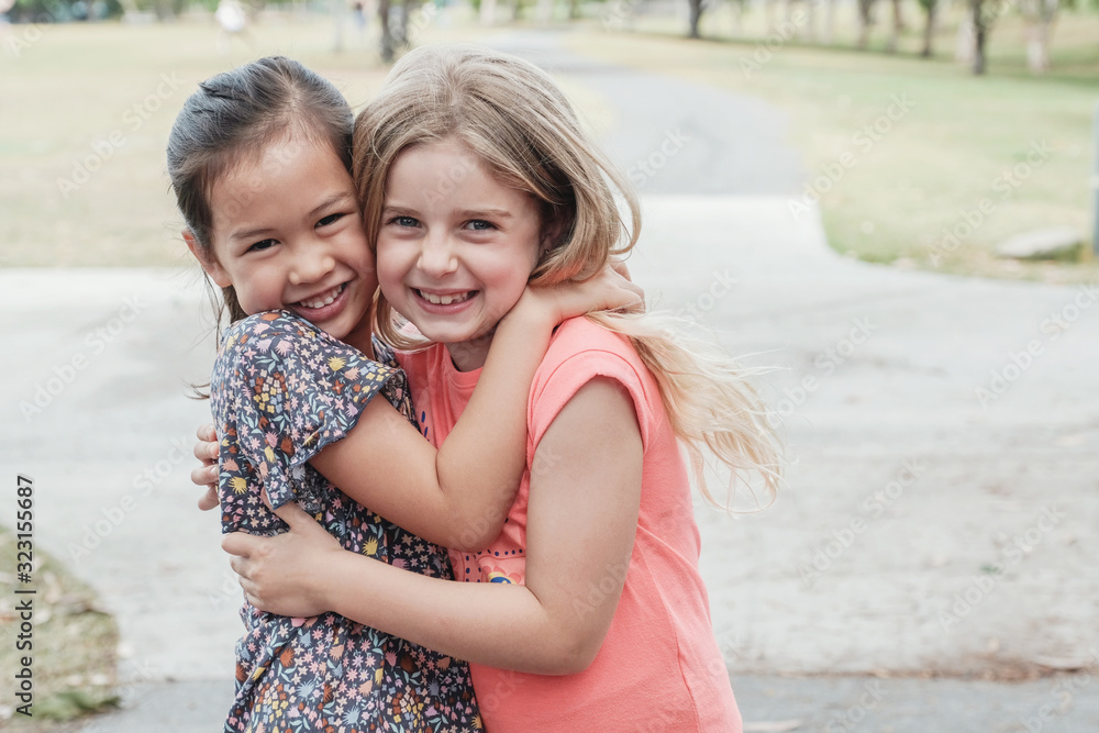Fototapeta Happy and healthy mixed race young little girls hugging and smiling in the park, best friend kids and children friendship concept
