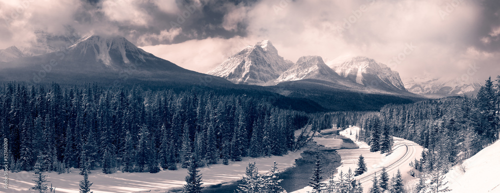 Fototapeta Banff National Park, Alberta, Canada. Iconic View of Morant's Curve with Canadian Rocky Mountains in the background during a vibrant winter day. Black and White