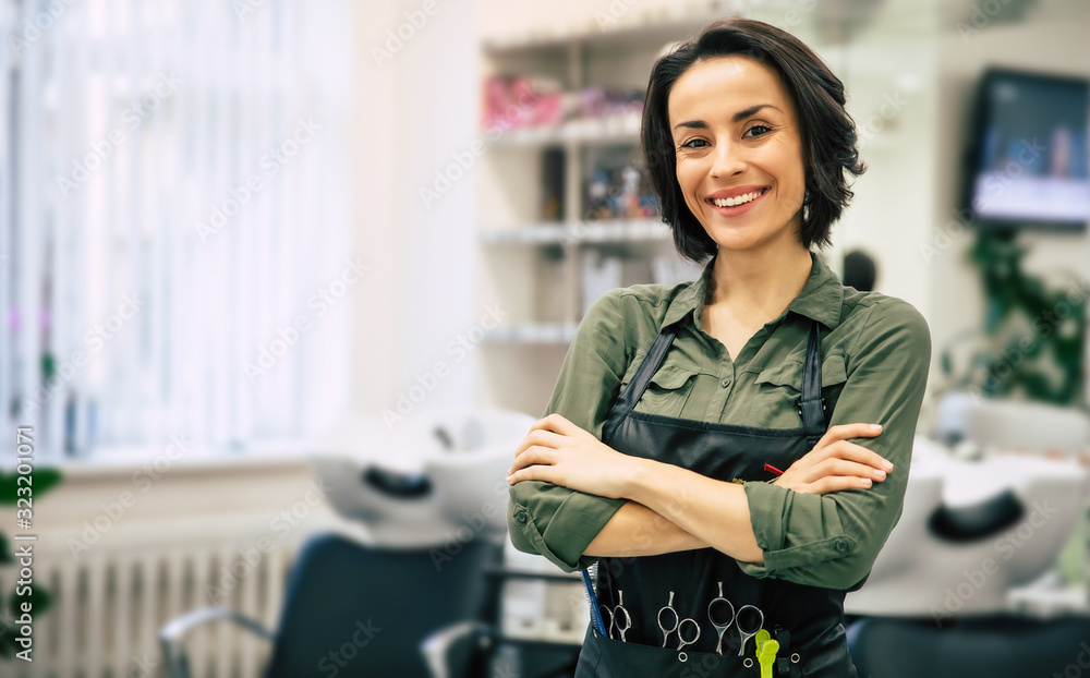 Fototapeta Smile of the professional. Portrait of a gorgeous young hairstylist standing with folded arms near her workplace in the salon.
