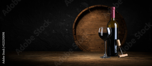 Expensive wine bottles collection and wooden barrel in the cellar, wine tasting and production concept - fototapety na wymiar