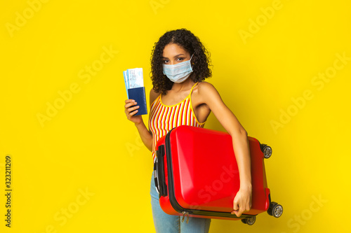 Girl mulatto tourist with a medical mask against a viral infection, coronavirus 2020, holding a passport with plane tickets and a suitcase Canvas