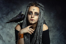 Portrait Of A Young Woman With Dreadlocks And With A Raven On Her Shoulder