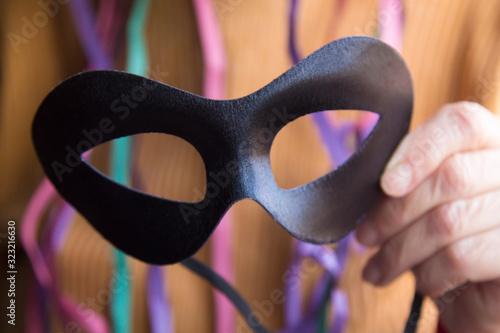 Fototapeta holding black carnival mask, carnival party concept obraz