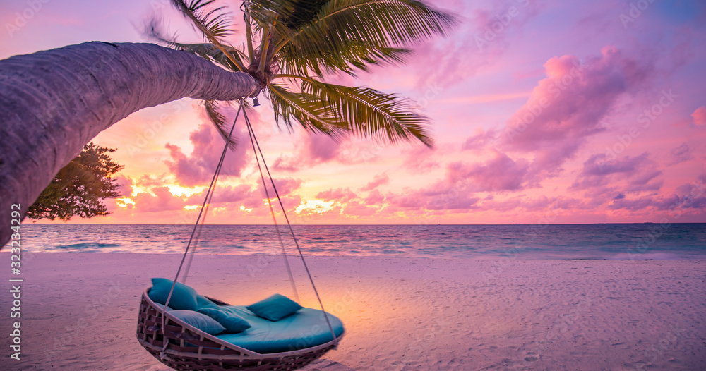 Fototapeta Tropical sunset beach background as summer landscape panorama with beach swing or hammock and white sand and calm sea beach banner. Perfect beach scene vacation or summer holiday concept