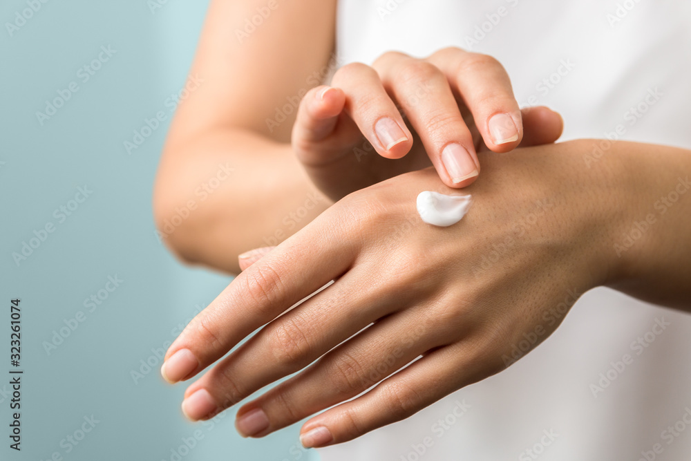 Fototapeta healthy hands and nails. seasonal skin protection. woman applying moisturizer on her hands