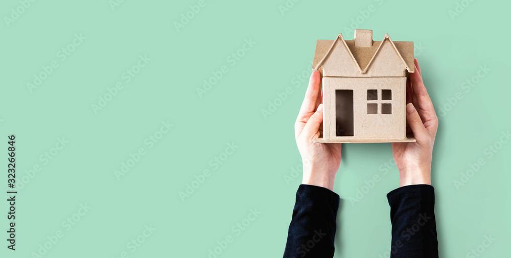 Fototapeta Woman holding a cardboard house overhead view