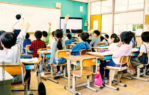 Photo 小学校の教室で手を挙げる生徒