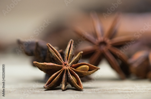 Fototapeta star anise with or without seed, closed, on a light wooden surface. spice for the recipe. beautiful picture, background. obraz