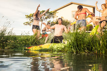 Group Of Friends With Slip And Slide Into A Swimming Lake. Bridger, Montana, USA