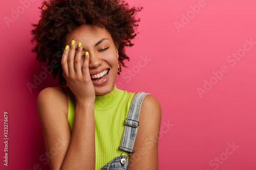 Headshot of carefree positive woman touches her face, laughs sincerely, hears fu Slika na platnu