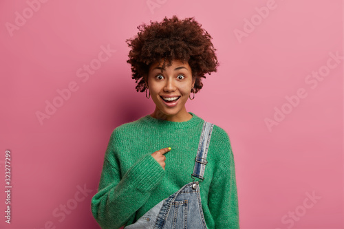 Modest happy surprised woman asks you talk about me, points at herself, doesnt expect being picked, smiles happily, dressed in fashionable wear, isolated on pastel rosy wall Wallpaper Mural