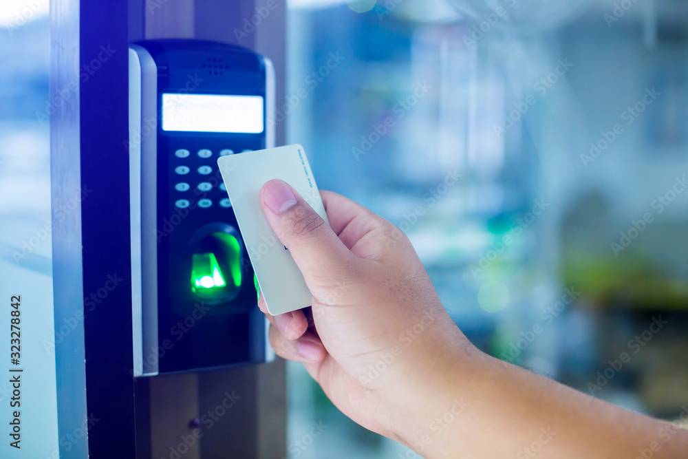 Fototapeta Door access control. Staff holding a key card to lock and unlock door at home or condominium. using electronic card key for access. electronic key and finger scan access control system to unlock doors