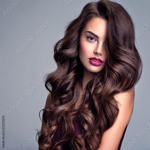 Face of a beautiful woman with long brown curly hair. Fashion model with wavy hairstyle. Attractive young girl with curly hair posing at studio. Female face with purple makeup. Violet make-up.
