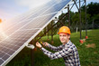 Leinwanddruck Bild Male engineer in helmet connecting solar panels, looking to the camera. Green ecological power energy generation. Modern solar, great design for any purposes. Business concept.