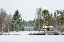 Wooden Cottage In Snow Covered Forest In Finland.