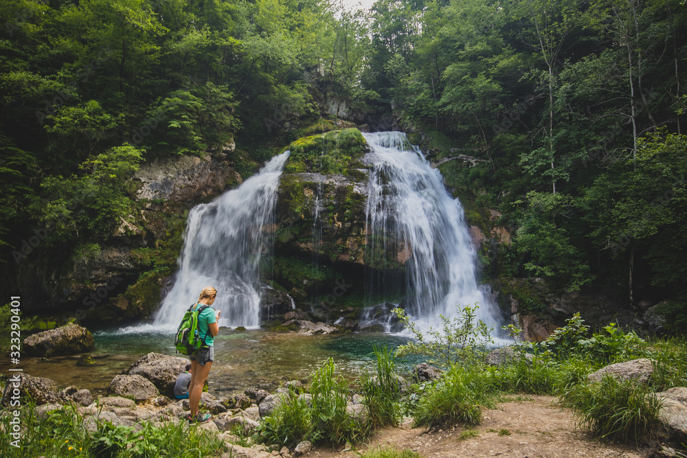 Blonde woman looking towards Virje waterfall in Slovenia, close to bovec. Dreamy and enchanting water falling down the cliff above the small alpine lake.