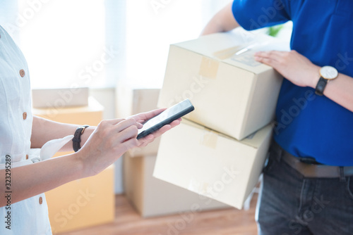 View of young asian woman appending signature in digital smart mobile phone after receiving parcel from courier delivery man at home Canvas Print