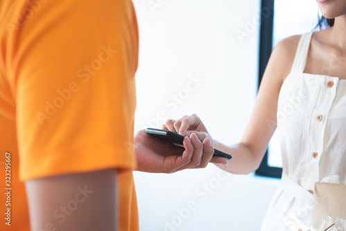 Photo View of young asian woman appending signature in digital smart mobile phone after receiving parcel from courier delivery man at home