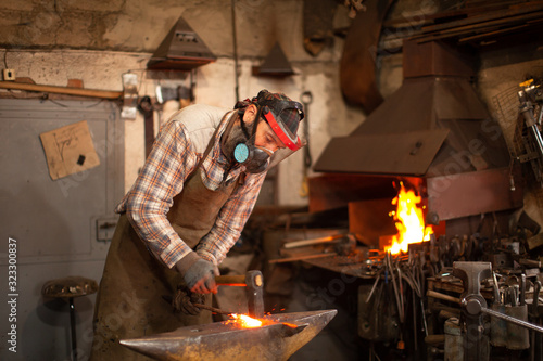 Vászonkép The blacksmith forging the molten metal on the anvil in smithy.