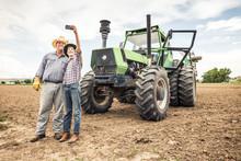 Farmer With Son In Plowed Fiel...