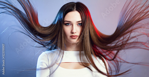 portrait of girl with long hair flying in air on studio background, young woman Wallpaper Mural