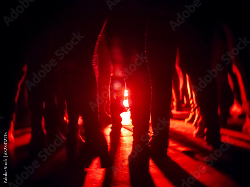 Silhouettes of feet in a nightclub against a bright red lantern in the center wi Wallpaper Mural