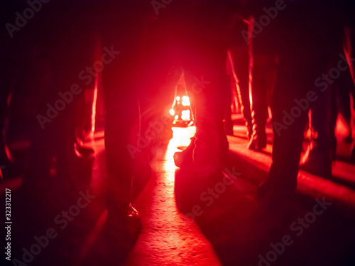 Silhouettes of feet in a nightclub against a bright red lantern in the center wi Canvas Print