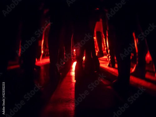 Canvas Print Silhouettes of feet in a nightclub against a bright red lantern in the center wi