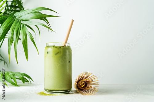 Photographie Making Japanese iced matcha latte, green tea with milk, soy milk, traditional matcha tools, with bamboo straw in glass on white background