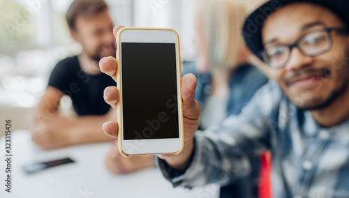 Obraz Young man sitting in cafe and showing smartphone - fototapety do salonu