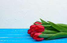 Bouquet Of Red Blooming Tulips With Green Stems And Leaves, Flowers Lie On A Blue Wooden Background