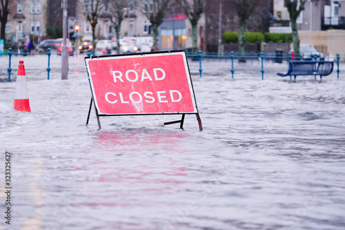 Road flood closed sign under deep water during bad extreme heavy rain storm weat Fototapeta