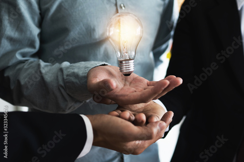 Innovation and idea of professional leader with teamwork holding lighting bulb, brainstorming teamwork and thinking management concept