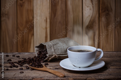 Fototapeta Coffee in a white cup and seeds Coffee on a wooden table obraz na płótnie