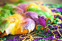 Mardi Gras King Cake With Yellow, Green, And Purple Sprinkles Surrounded By Mardi Gras Beads And A Glittering Fleur De Lis.