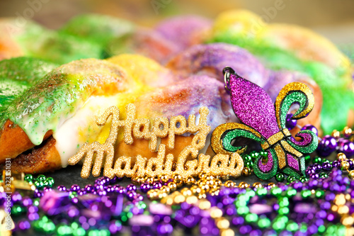 Happy Mardi Gras text in gold glitter and a king cake with yellow, green, and purple sprinkles surrounded by Mardi Gras beads and a glittering fleur de lis. - 323351031