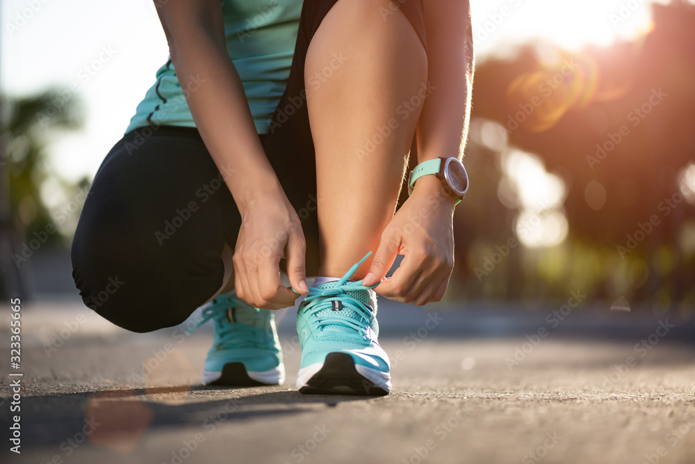 Fototapeta Running shoes - closeup of woman tying shoe laces. Female sport fitness runner getting ready for jogging in garden background.