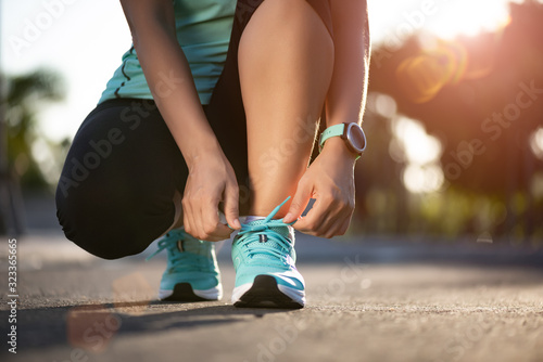 Fotomural Running shoes - closeup of woman tying shoe laces