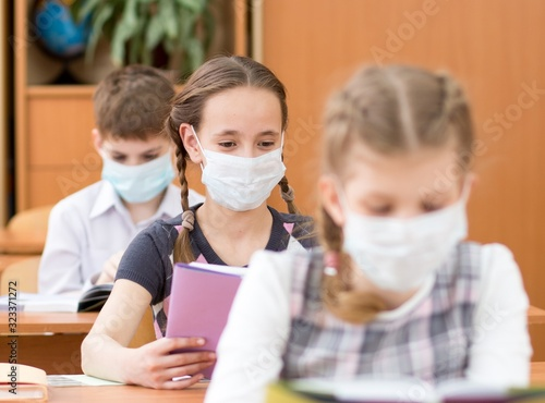 Schoolkids with medicine mask on faces against virus or flu in classroom - 323371272