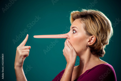 Photo Woman touching her long nose because of lie
