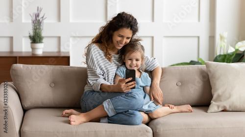 Obraz Happy pretty mommy cuddling small daughter, taking selfie on cellphone. - fototapety do salonu