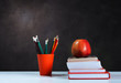Back to school, orange pencil holder, stack of books on white table with red apple, empty black school board background, education concept.