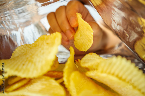Fotografía Hand hold potato chips inside snack foil bag