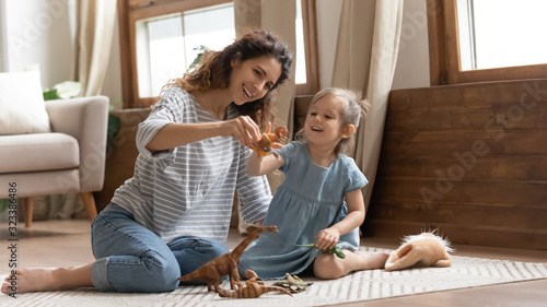 Overjoyed family of two playing with toys on floor carpet. Canvas Print